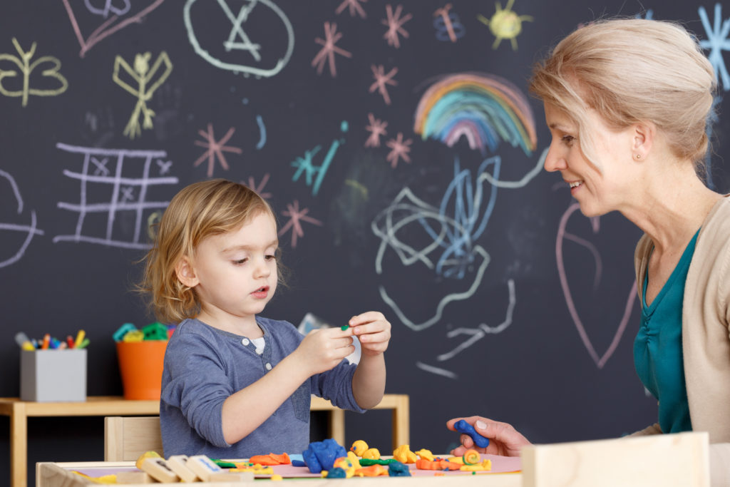 Young preschool teacher leading art classes with little girl