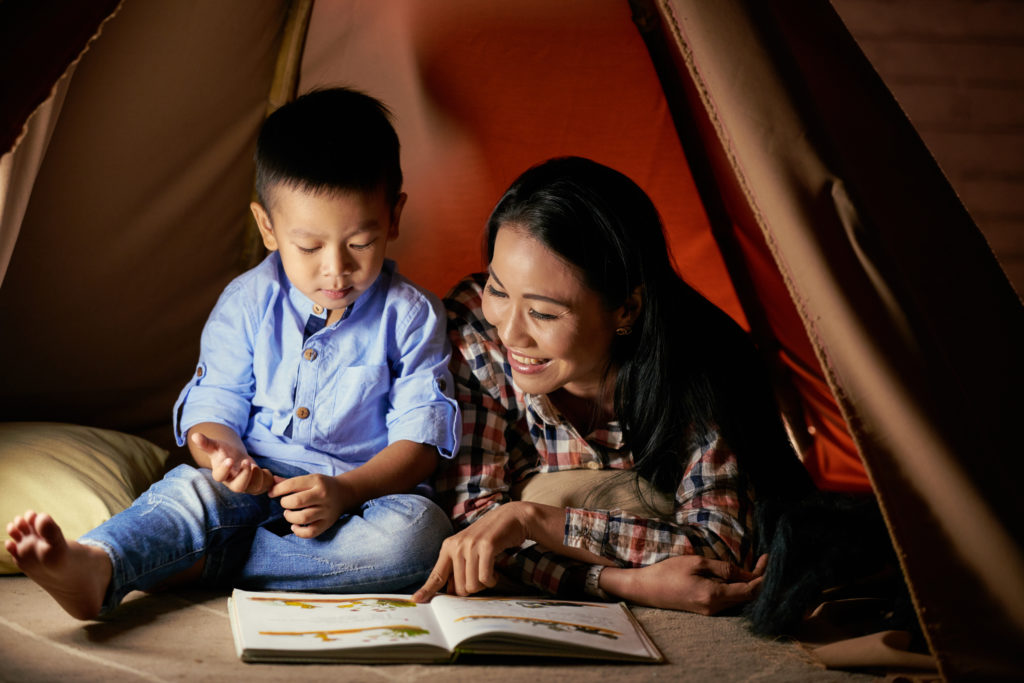 Cute Asian little boy listening to his mother reading fairytale