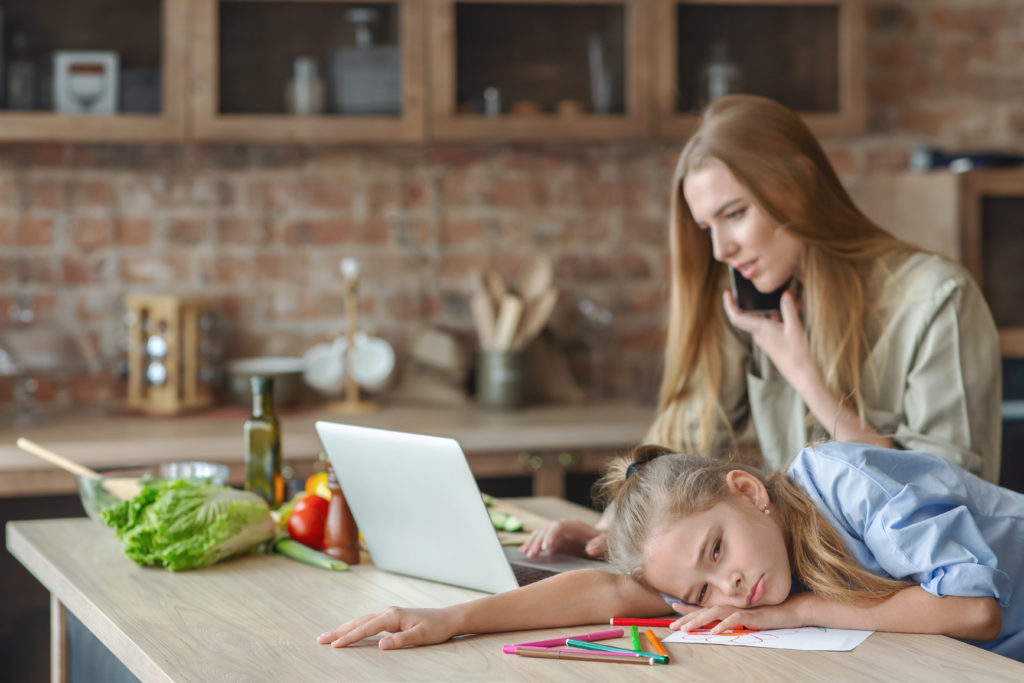 Sad little girl feeling bored while mother working from home