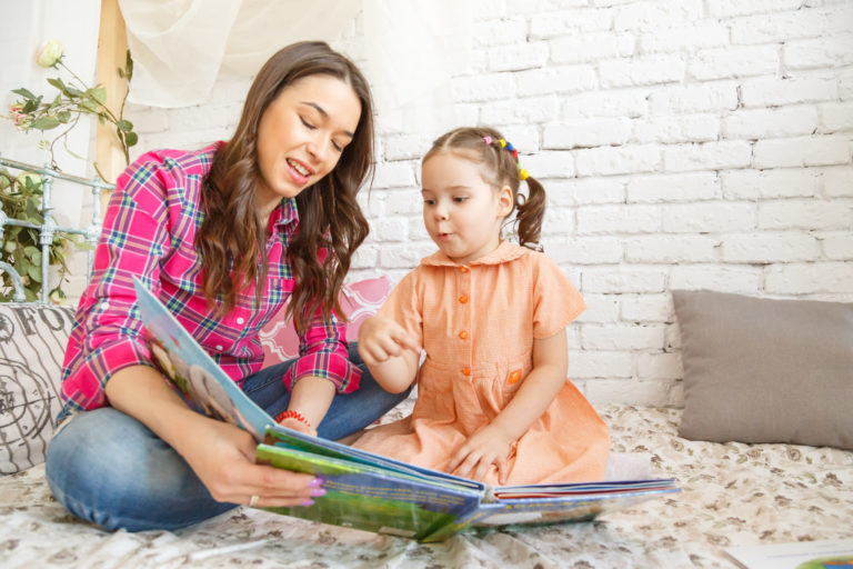 Young mother and her child girl reading a book